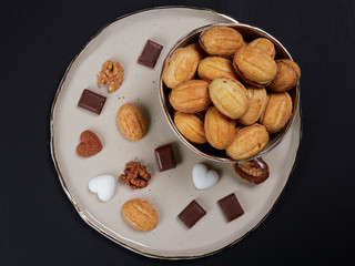 Walnut shaped cookies on a plate, with bits of chocolate, heart shaped sugar cubes and walnuts. Russian oreshki. Flat lay.