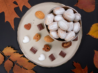 Walnut shaped cookies on a plate, with pieces of chocolate, heart shaped sugar cubes and walnuts. Russian oreshki.