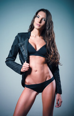 Studio fashion shot: lovely sexy young girl dressed in black underwear and jacket