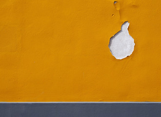 bright yellow textured paint on a wall with cracks and hole flaking away and grey horizontal stripe at the bottom