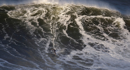A surfer drops in a large wave at Praia do Norte in Nazare