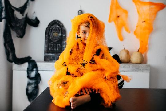 Little boy wrapped in orange spider web at Halloween