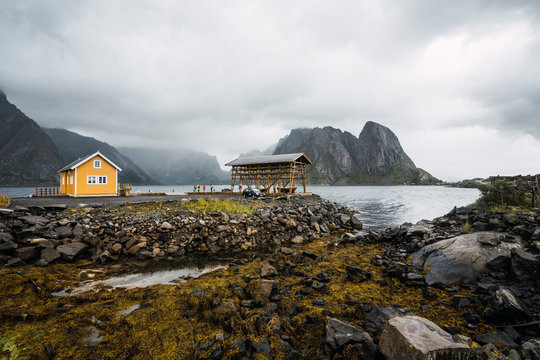 Scenic view of house at rocky coast against mountain and cloudy sky
