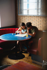 Young couple sitting at table in a cafe with map