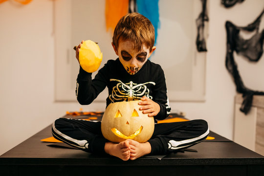 Portrait of little boy with painted face and fancy dress sitting on table looking inside of Jack O'Lantern
