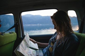 Young woman sitting on backseat in a car looking at map