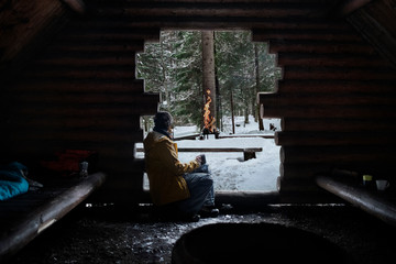 Finland, Kuopio, woman sitting in wooden hut in winter looking at campfire