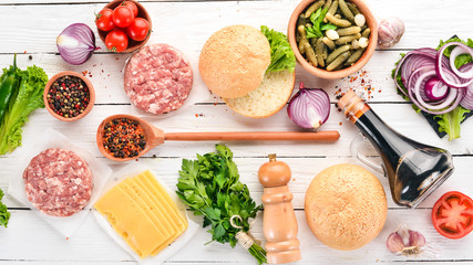 Preparation of burger. Meat, tomatoes, onions. On a white wooden background. Top view. Free copy space.
