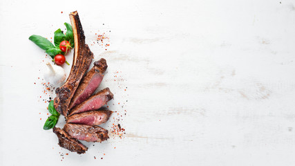 Tuinposter Steakhouse Steak on the bone. tomahawk steak On a white wooden background. Top view. Free copy space.
