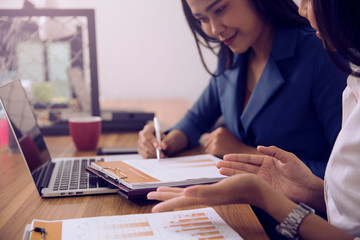 An Asian business woman is sitting with her financial adviser on a business plan.