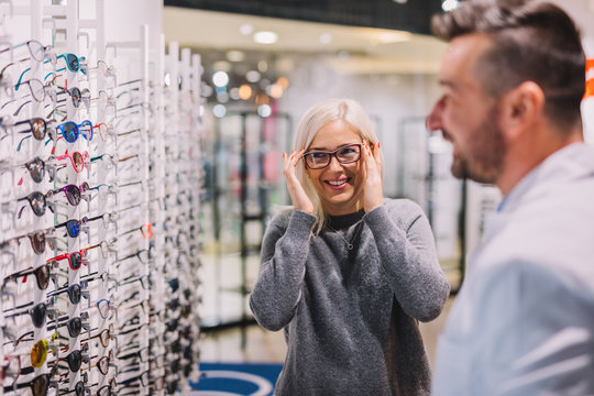 Optician and client choosing glasses together.