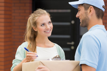 Smiling friendly courier in blue uniform giving package to happy woman signing receipt