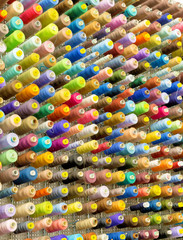 Organized wall of spools with sewing threads in many color variations