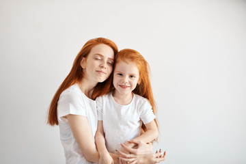 Happy family concept. Beautiful young mother with long loose red hair embracing her cute little 4 year old girl, feeling tenderness and deep love looking at camera isolated at studio over white