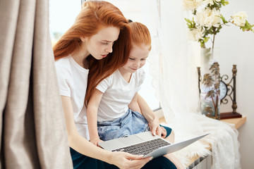 Happy redheaded mother and daughter spending time together , Mom helps her sweety to do homework using laptop computer at home at white and well-lit living room