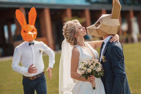 Fun outdoor wedding party. Young beautiful bride and groom in the mask of a rabbit kiss.