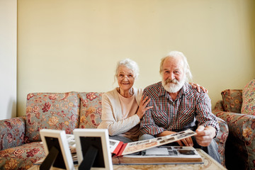 Happy grey haired wrinkled woman being pleased to meet her first love, leans at senior man s shoulder, while looking through photo album, remembering pleasant moments of their relatioship.