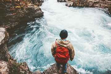 Man traveling with backpack alone in Sweden active lifestyle hiking in river canyon adventure vacations outdoor