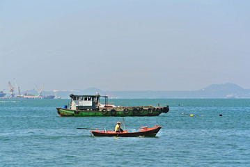 Tranquil Scenery of Small Colorful Boat In Front of Green Fisherman Boat in the Sea