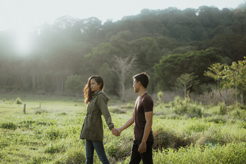 happy young asian couple in countryside enjoying nature