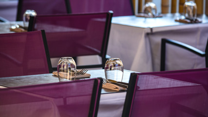 Table set with crystal glasses. View of tables with clear glasses and cutlery set for lunch in modern restaurant