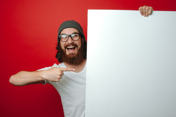 Portrait of cheerful bearded hipster man pointing at white blank paper
