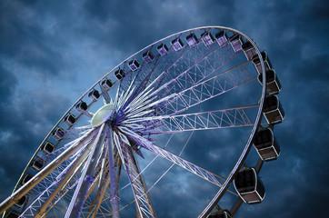 Big luminous ferris wheel in front of dark blue dramatic sky