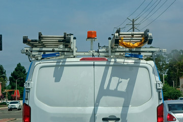 The back end of a white utility van carrying ladders on its racks. Wall mural