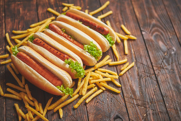 American hot dogs assorted in row. Served with french fries. Placed on wooden table. Above view on a rustic wood background