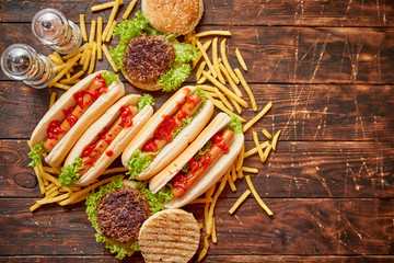 Fastfood assortment. Hamburgers and hot dogs placed on rusty wood table. Served with french fries. View from above.