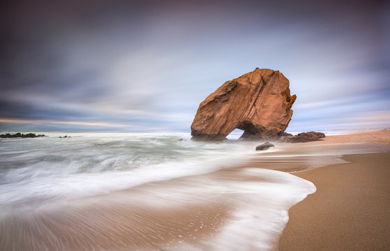 Magestic rock and the waves at the sunset
