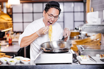 hungry chef in the kitchen. close up photo. man with wide opened mouth is going to eat noodle