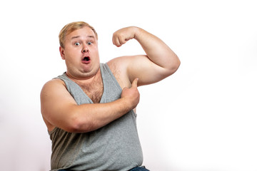 Offensed disapponted obese caucasian man showing his plump fatty arms like bodybuilders do, isolated over white background. Fat and slim man, weight loss concept