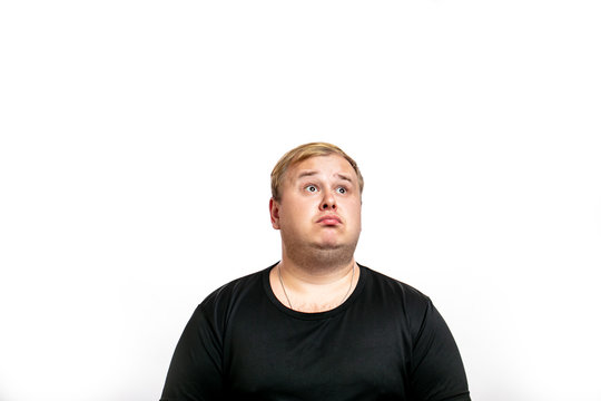 Big fat stout blonde man dressed in black t- shirt looking up with surprised expression, human emotions concept. Isolated on white background with copyspace.