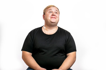 Excited kind-hearted chubby overweight man feeling happy looking up at blank space for ptomotion text. Obesity, gluttony and unhealthy lifestyle