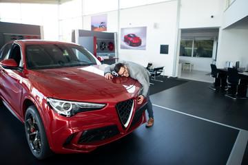 Happy customer buying luxury modern SUV car at vehicle dealership.