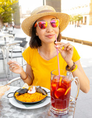 Young traveler woman eating spanish dinner sea Paella and sangria fruit wine during siesta