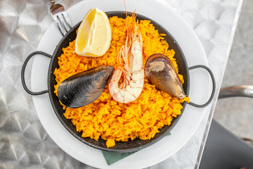 Delicious spanish seafood paella in traditional pan on the table in cafe