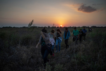Migrants from Central America cover faces after illegally crossing into the United States from Mexico in Penitas, Texas