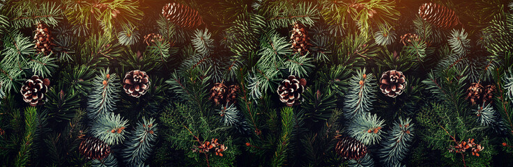 Fototapete - Holiday background of Christmas tree branches, spruce, juniper, fir, larch, pine cones with light. Xmas and New Year theme. Top view, wide composition, seamless pattern