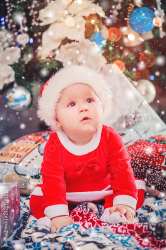 Baby first Christmas holidays. Baby with Santa hat with gift. Living room  decorated by Christmas tree and gift boxes. Xmas and New Year theme ce5803538aa4
