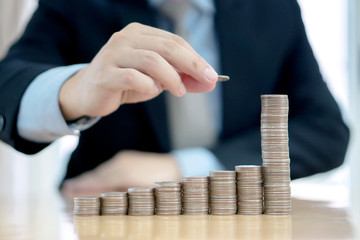 Businessman Sitting at Desk and Stacking Coins