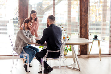 Young caucasian couple consulting with bank financial adviser before buying new house. Two bearded men sitting at table and checking documents while woman stands behind.