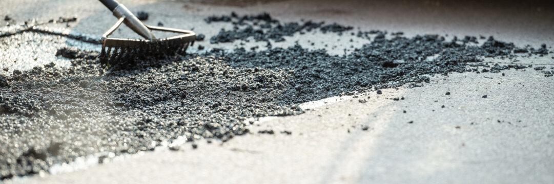 Wide view image of rakes arranging fresh asphalt mixture
