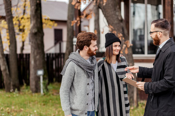 Friendly male real estate agent in formal wear standing outdoor, in front of the private house, handing house key to a young excited couple dressed in warm autumn clothes