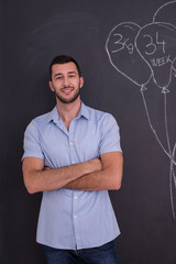 portrait of man in front of black chalkboard