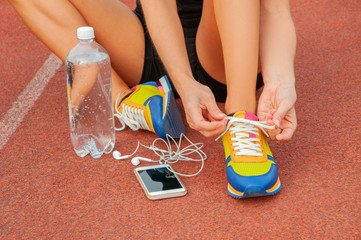 Workout concept. Sports woman runner tying shoelaces.