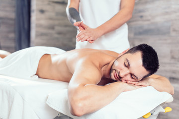 masseur preparing his hands for massage while his clent li lying with closed eyes. close up side view photo