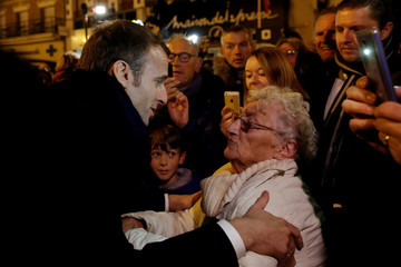 French President Emmanuel Macron talks with a woman in the crowd as he arrives at the city hall in Peronne