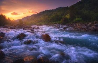 beautiful sunrise over fast flowing mountain river